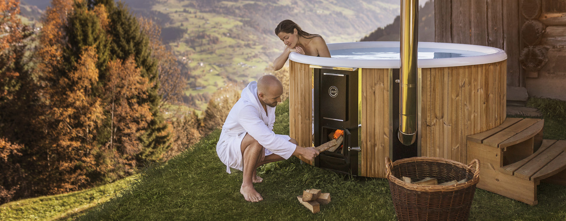 A women sitting in the hot tub that is placed next to a wooden house, while a man is firing up the stove