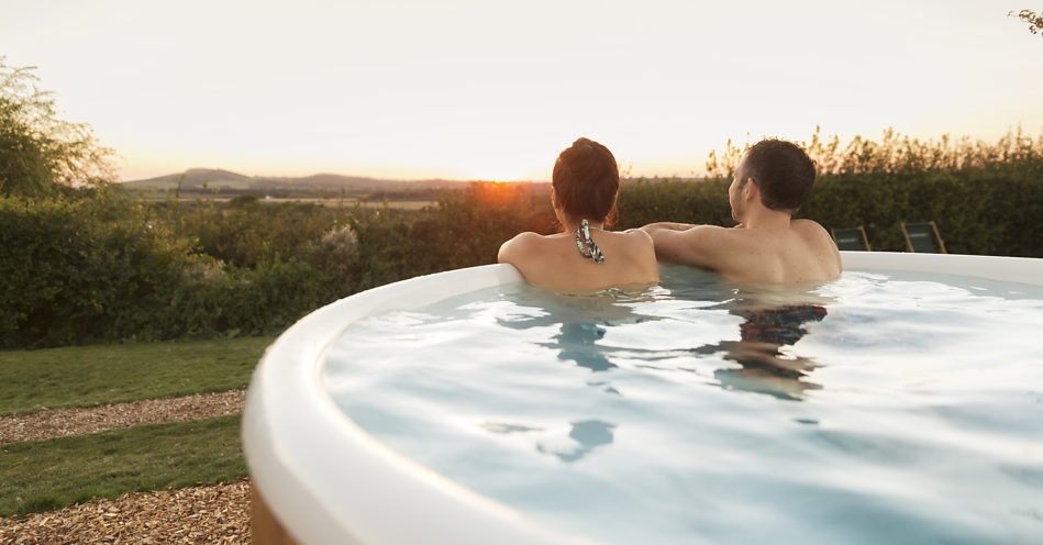 A close up of the back of a men and women, who are sitting in the hot tub and observing the surrounding area