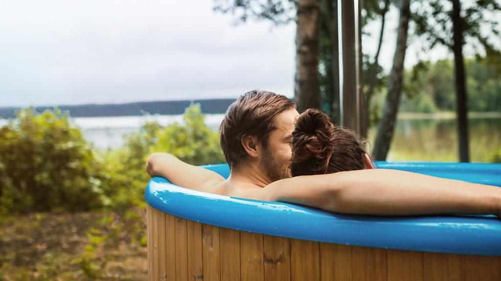A couple enjoying a warm bath in a hot tub in Swedish nature
